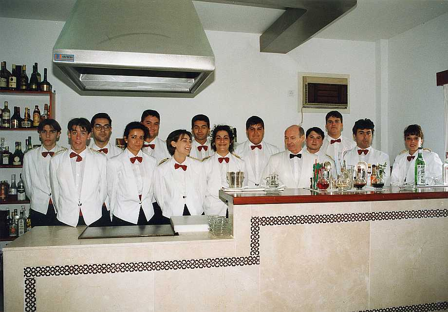 Un grupo de alumnos con el profesor de Bar, Sr. Amézquita, en el Aula de Bar, preparada también para prácticas de cafetería. Puede verse el mostrador cortado para dejar a la vista la plancha, dónde hacer sandwiches y platos combinados.